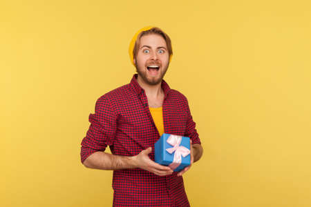 Amazed happy hipster guy in checkered shirt holding gift box, smiling looking at camera with surprised excited joyful expression, congratulating on birthday anniversary. indoor studio shot isolated