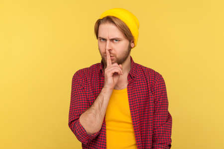 Shh, be quiet! Hipster bearded guy in beanie hat and checkered shirt shushing with finger on lips hand gesture, asking for silence secrecy, mute turn down sound. indoor studio shot isolated on yellow