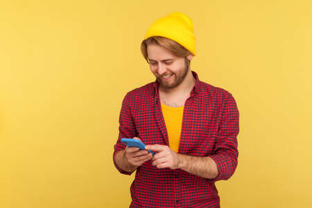 Happy trendy hipster guy in beanie hat and checkered shirt using cell phone, texting or reading message, smiling while chatting in social network, enjoying mobile app. indoor studio shot isolated Stock fotó