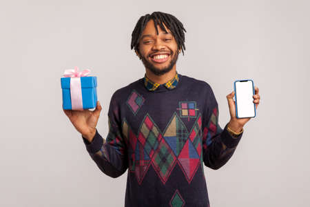Cheerful pleased african guy with dreadlocks holding empty blank smartphone and gift box in hands with toothy smile on face, online shopping, bonuses. Indoor studio shot isolated on gray background