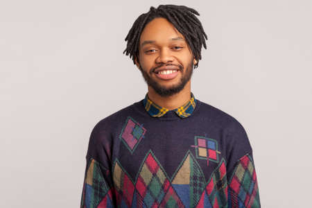 Cheerful african man in casual style sweatshirt with dreadlocks looking at camera with healthy toothy smile, satisfied with life, success. Indoor studio shot isolated on gray background
