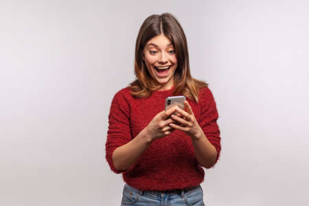 Amazed brunette girl in shaggy sweater using mobile phone with surprised expression, typing or reading shocking message on social network, online communication. studio shot isolated on gray background Stock fotó