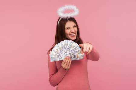 Cheerful brunette woman with halo above her head holding dollar banknotes pointing finger at you with toothy smile, lottery winner, success. Indoor studio shot isolated on pink background Banque d'images