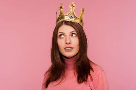 Closeup egoistic self confident woman wearing golden crown on head, looking with arrogance, pretending to be queen, leadership. Indoor studio shot isolated on pink background