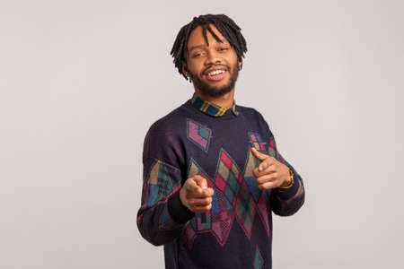 Hey you! Satisfied handsome guy with dreadlocks pointing fingers at camera and looking with toothy smile, flirting, admiring. Indoor studio shot isolated on gray background