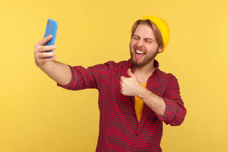Cheerful trendy hipster guy in checkered shirt showing thumbs up, approval gesture, smiling talking video call or streaming on mobile phone, asking follow and like his blog. studio shot isolated Stock fotó