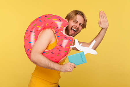 Optimistic tourist guy in undershirt standing with pink donut rubber ring, holding passport document and airplane mockup, waving hello hi or goodbye gesture, hurry to travel. studio shot isolated