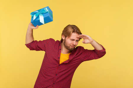 Positive man in checkered shirt holding gift ready to throw box, keeping hands over eyes looking far away, peering into distance, waiting future holidays. studio shot isolated on yellow background Stock fotó