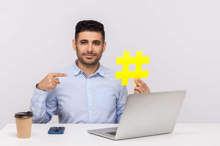 Businessman in elegant shirt sitting in office workplace with laptop, pointing big hashtag symbol and smiling at camera, hash sign of viral internet idea, web seo promotion. studio shot isolated