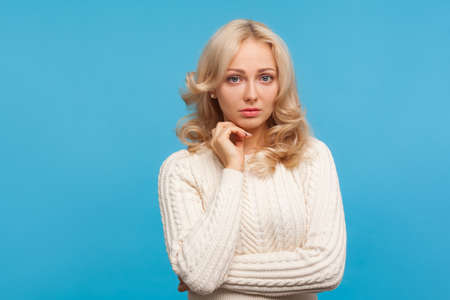 Unhappy depressed woman with curly blond hair looking at camera, sorrowful concerned about breakup or divorce. Indoor studio shot isolated on blue background