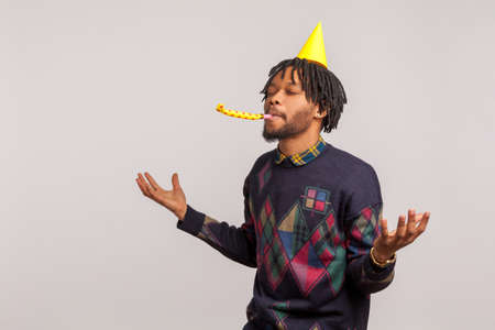 Pleased satisfied african man with dreadlocks in party hat having fun and enjoying blowing party horn with closed eyes, birthday celebration. Indoor studio shot isolated on gray background