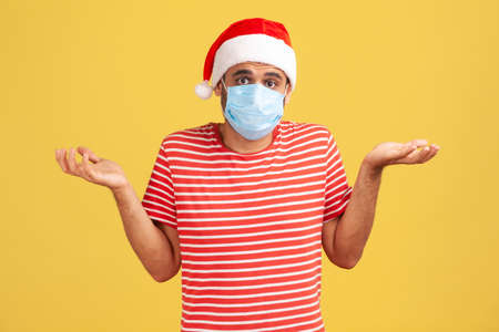 Puzzled man in red t-shirt and santa claus hat with protective face mask shrugging shoulders, dont know how to celebrate holidays because of corona virus. Studio shot isolated on yellow background