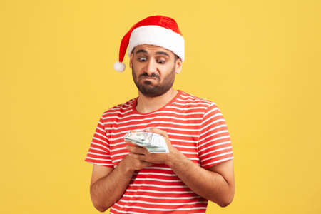 Unhappy confused bearded man in santa claus hat holding dollars in hands, greedy to buy holiday gifts. Indoor studio shot isolated on yellow background
