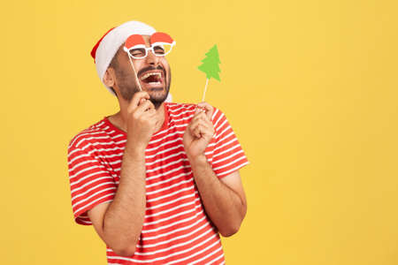 Extremely happy man in red santa claus hat laughing trying on party christmas masks on sticks, celebration. Indoor studio shot isolated on yellow background Banque d'images