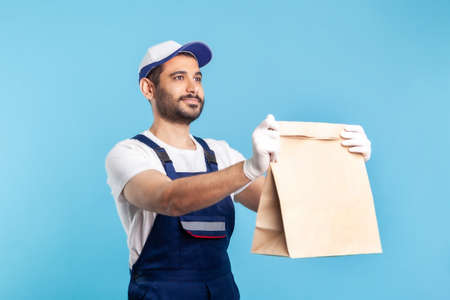Portrait of cheerful bearded handyman in overalls and gloves giving ordered parcel. Courier delivering food in paper bag, post mail services. indoor studio shot isolated on blue background