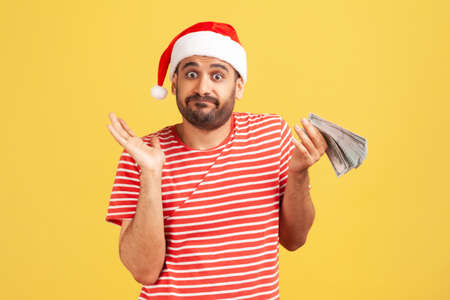 Puzzled confused man with beard in red santa claus hat holding cash in hands, dont know how to spend his allowance, holidays perks. Indoor studio shot isolated on yellow background Zdjęcie Seryjne