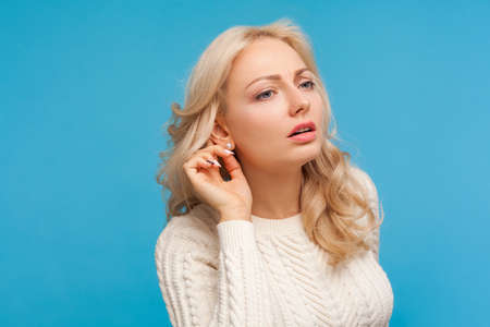 Closeup curious nosy blond woman in white sweater holding hand near ear trying to hear secret information, overhearing private conversation. Indoor studio shot isolated on blue background 版權商用圖片