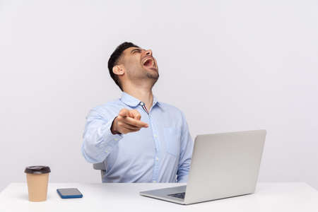 Amused delighted businessman sitting office workplace with laptop on desk, pointing finger to camera and laughing out loud, noticing teasing ridiculous coworker. indoor studio shot isolated on white
