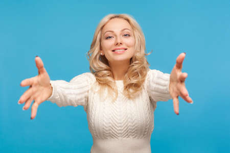 Come here and hug me. Happy attractive woman with curly blond hair spreading arms ready to embracing, excitement. Indoor studio shot isolated on blue background