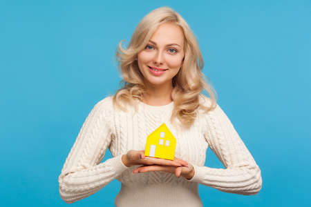 Smiling blond woman real estate agent demonstrating model of paper house to camera, property crediting, loan. Indoor studio shot isolated on blue background Archivio Fotografico