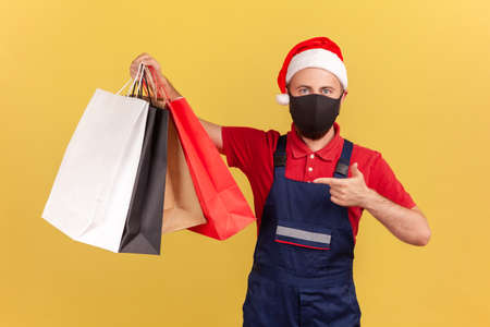 Male courier in protective medical mask and holiday santa claus hat pointing finger at shopping bags in hand, easy delivery during quarantine. Indoor studio shot isolated on yellow background