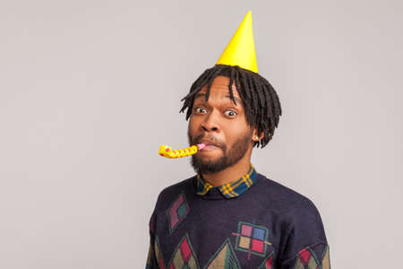 Closeup african man with dreadlocks wearing party cone cap and blowing party pipe, celebrating anniversary, hungout. Indoor studio shot isolated on gray background