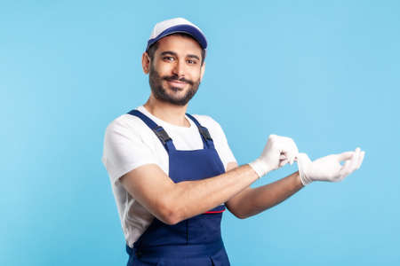 Happy handyman in overalls showing hand with surgical gloves, smiling to camera. Safety clothes, protection and hygiene in service industry, courier delivery, housekeeping maintenance. studio shot
