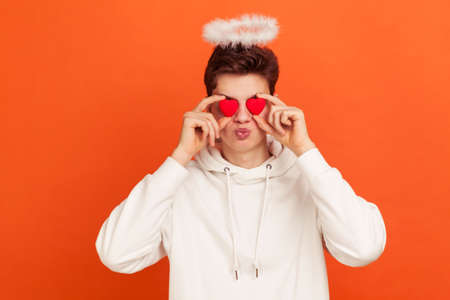 Adorable teenager in casual style hoodie with halo overhead sending kisses holding toy hearts near eyes, man celebrating saint valentine day. Indoor studio shot isolated on orange background