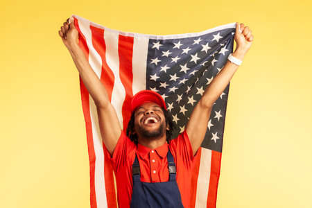 Extremely happy satisfied craftsman in uniform holding flag of united states of America, celebrating labor day, independence. Indoor studio shot isolated on yellow background