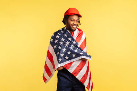 Positive afro-american man in red cap with dreadlocks standing wrapped in American flag looking at camera and smiling, proud of his country. Indoor studio shot isolated on yellow background