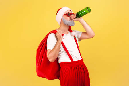 Mischievous naughty drunk adult man with big red bag and santa claus hat drinking beer from bottle, having fun, relaxing after holidays. Indoor studio shot isolated on yellow background