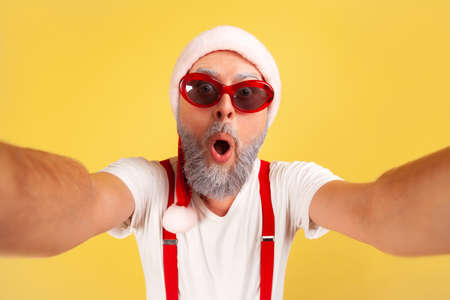 Closeup surprised grey bearded man in santa claus hat and sunglasses looking into camera with amazed shocked expression, making selfie. Indoor studio shot isolated on yellow background
