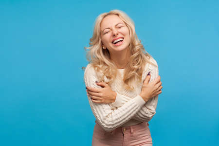 Positive optimistic woman with blond curly hair hysterically laughing enjoying life and freedom, carefree female. Indoor studio shot isolated on blue background