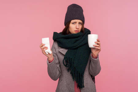 Sick unhealthy woman in scarf and hat holding in hands napkin and cup with hot tea, feeling chills. Indoor studio shot isolated on pink background