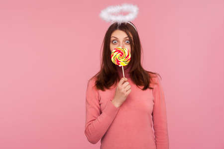 Surprised playful brunette woman with angelic halo holding big colorful lollipop near mouth, having fun eating rainbow candy. Indoor studio shot isolated on pink background