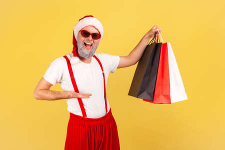 Excited satisfied adult man in santa claus hat and sunglasses showing colorful paper shopping bags, holidays purchases. Indoor studio shot isolated on yellow background