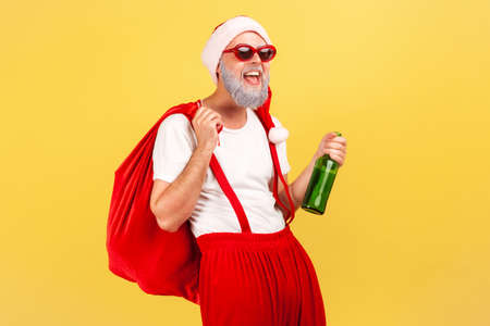 Happy elderly man in santa claus hat, trendy sunglasses and pants with suspenders holding bottle with alcohol and big red bag, celebration, bad habit. Indoor studio shot isolated on yellow background