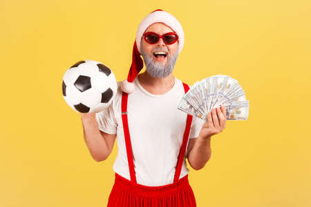 Satisfied elderly man in santa claus hat and stylish sunglasses holding soccer ball and dollar banknotes, sports betting, big win. Indoor studio shot isolated on yellow background Stock Photo