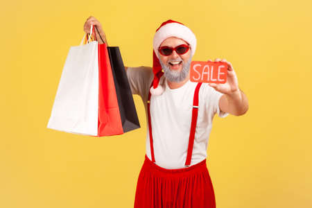Satisfied grey bearded man in stylish sunglasses and santa claus costume holding and showing paper shopping bags and sale card, holidays discounts. Indoor studio shot isolated on yellow background