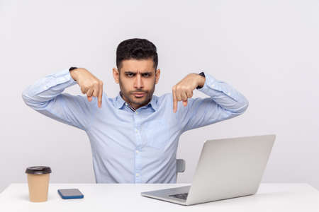 Here and right now, immediately! Angry boss sitting office workplace with laptop on desk, pointing fingers down giving order, control and authority concept. studio shot isolated on white background