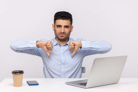Dislike! Displeased businessman sitting office workplace showing thumbs down gesture, expressing disapproval, bad feedback, negative service rating. indoor studio shot isolated on white background Archivio Fotografico