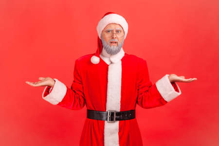 Disappointed portrait of confused gray bearded elderly man in eye glasses and santa claus costume throws up hands, cant understand how to spend holidays. Indoor studio shot isolated on red background