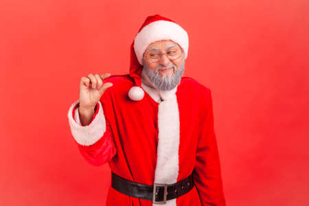 Portrait of dissatisfied elderly gray bearded man in santa claus costume showing a little gesture with fingers, skeptical about winter holidays magic. Indoor studio shot isolated on red background