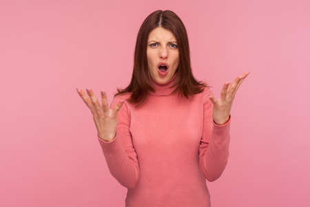 Nervous disappointed brunette woman in pink sweater spreading hands and shouting asking what do you want from me? Indoor studio shot isolated on pink background