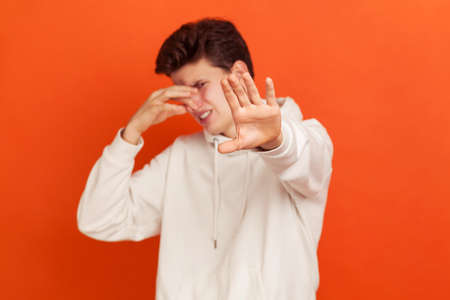 Confused young man in hoodie grabbing nose with fingers and showing stop gesture, feeling disgusting unpleasant smell. Indoor studio shot isolated on orange background