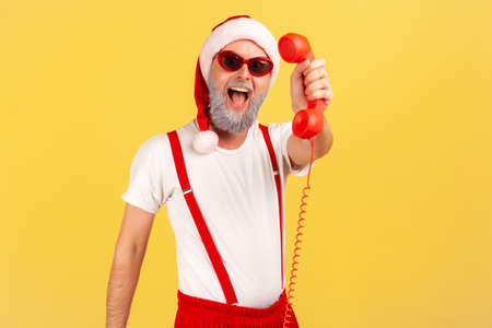 Excited happy gray bearded man in sunglasses and santa claus hat holding and showing landline telephone handset, calling to congratulate with fests. Indoor studio shot isolated on yellow background Stock fotó
