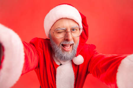Closeup smiling positive gray bearded man in eyeglasses and santa claus costume looking at camera and winking, making selfie. Indoor studio shot isolated on red background Standard-Bild