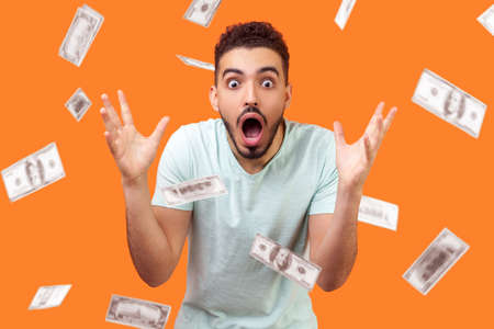Oh my god, wow! Portrait of amazed man looking at camera with big eyes and open mouth, absolutely shocked of money rain falling from up. indoor isolated on orange background