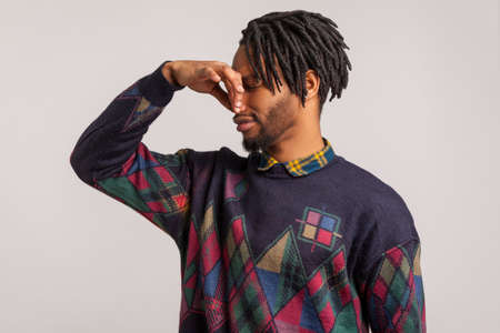 Profile portrait bearded african guy with dreadlocks pinching his nose with fingers feeling unpleasant disgusting odor, spoiled food. Indoor studio shot isolated on gray background