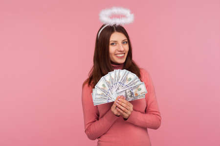 Happy angelic woman with halo above head holding and showing dollar banknotes, boasting big lottery win. Indoor studio shot isolated on pink background